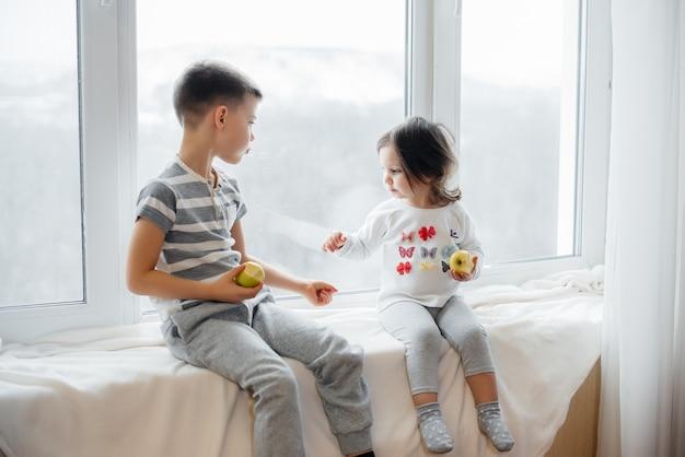 Hermano y hermana están sentados en el alféizar de la ventana jugando y comiendo manzanas. felicidad