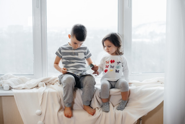 Hermano y hermana están sentados en el alféizar de la ventana y leen un libro. felicidad, familia