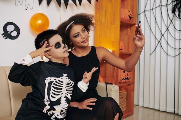 Hermano y hermana hablando de fotos en el teléfono inteligente o videollamadas a amigos en la fiesta de halloween en casa