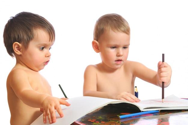 Hermano y hermana jugando con lápices de colores juntos