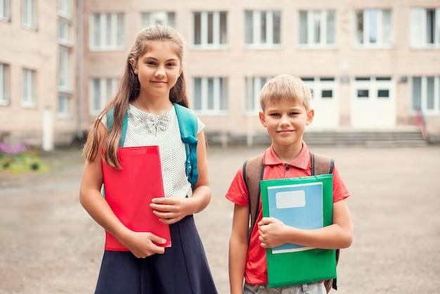 Hermano y hermana con materiales de aprendizaje y mochilas cerca de la escuela.