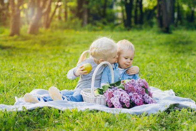 Hermano y hermana sentada en el prado de verano