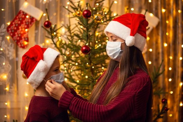 Hermano y hermana con sombreros navideños, suéteres burdeos y máscaras médicas cerca de abeto decorado