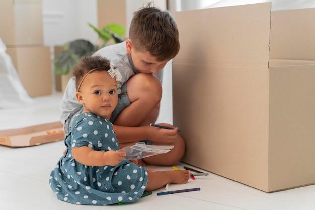 Hermano lindo jugando juntos antes de mudarse con sus padres