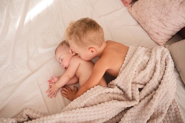 Hermano mayor besando a recién nacido vista superior