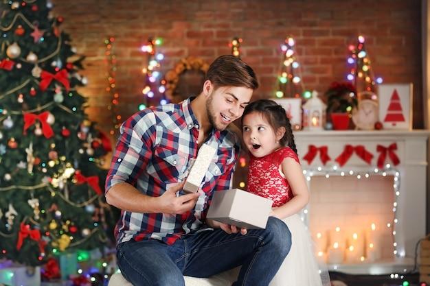 Hermano mayor y hermana pequeña abriendo el regalo en el salón de navidad