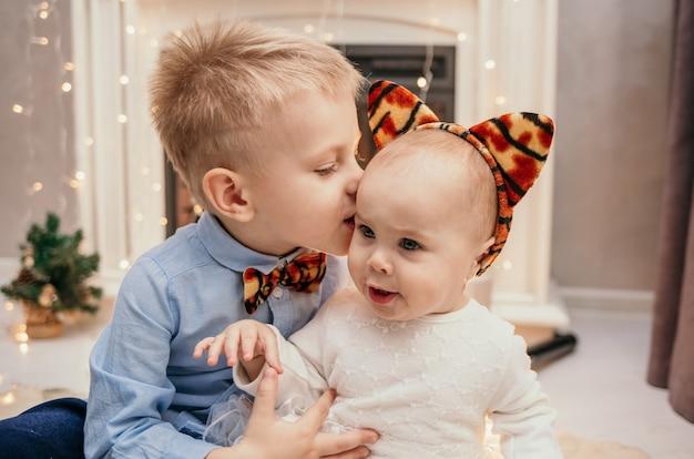 Un hermano pequeño besa a la hermana de un bebé cerca de la chimenea de año nuevo en la habitación.
