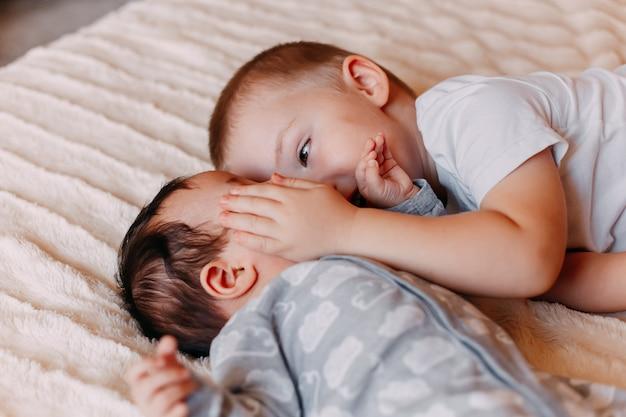 El hermano y su hermana pequeña y alegre acostados en la cama bostezan