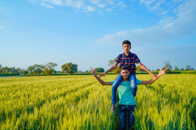 Hermano superpuesto a su hermano pequeño en campo de trigo, india rural