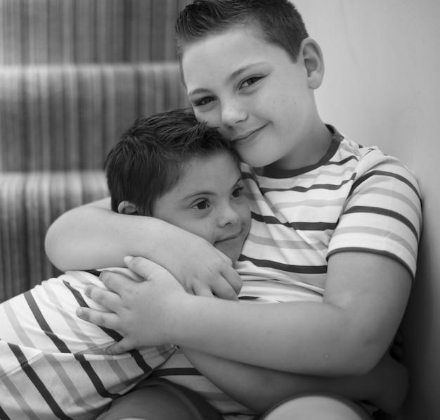 Hermanos abrazándose en las escaleras.