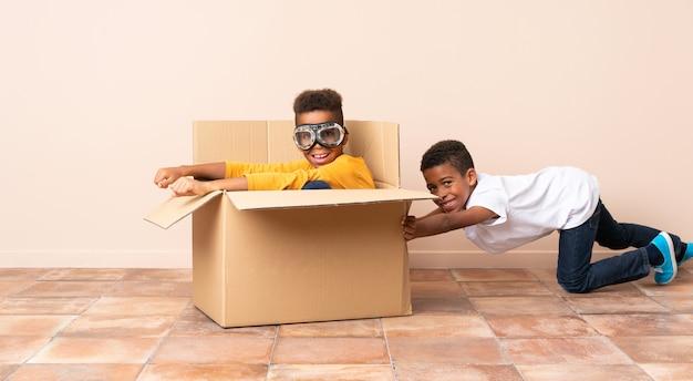 Hermanos afroamericanos jugando. chico dentro de una caja de cartón con gafas de aviador