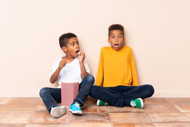 Hermanos afroamericanos con palomitas de maíz y haciendo gesto de sorpresa
