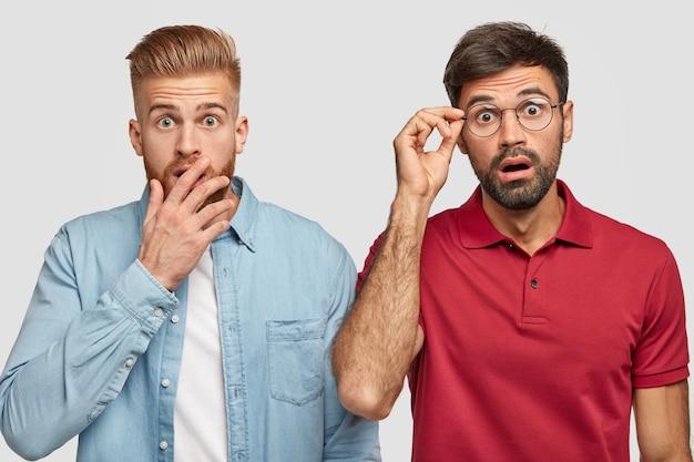 Hermanos barbudos conmocionados posando contra la pared blanca