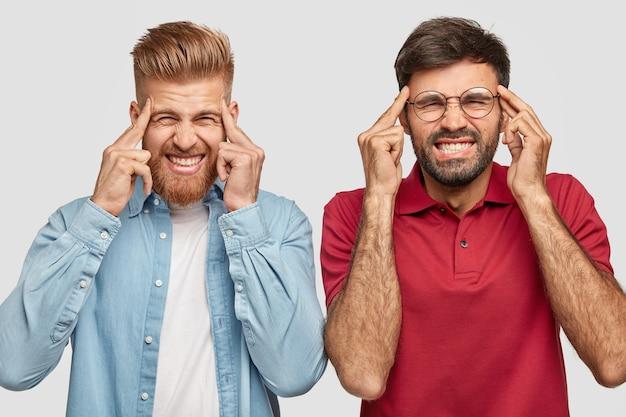 Hermanos barbudos frustrados posando contra la pared blanca
