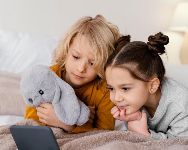 Hermanos en la cama viendo videos en el teléfono