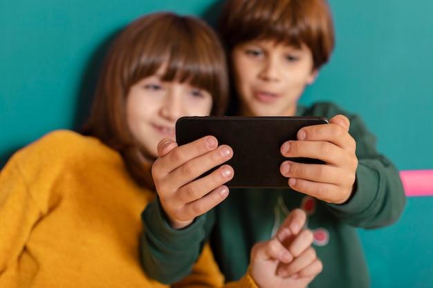 Hermanos en casa usando móvil