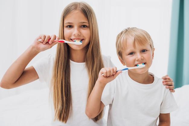 Hermanos cepillando sus dientes juntos