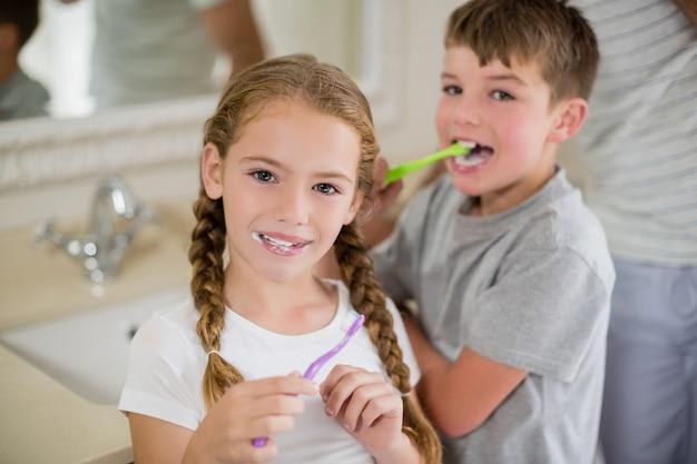 Hermanos cepillarse los dientes en el baño.