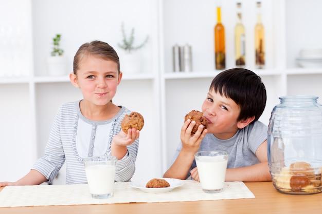 Hermanos comiendo galletas y bebiendo leche
