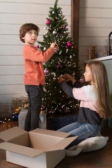 Hermanos decorando el árbol de navidad juntos