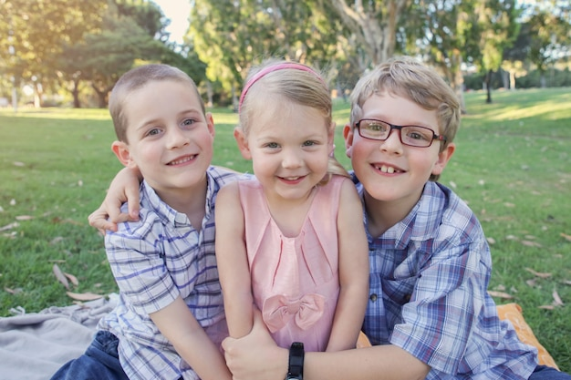 Hermanos felices y hermana jugando en el parque