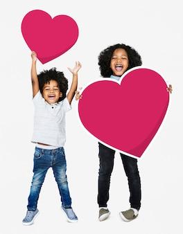 Hermanos felices saltando con iconos de corazón