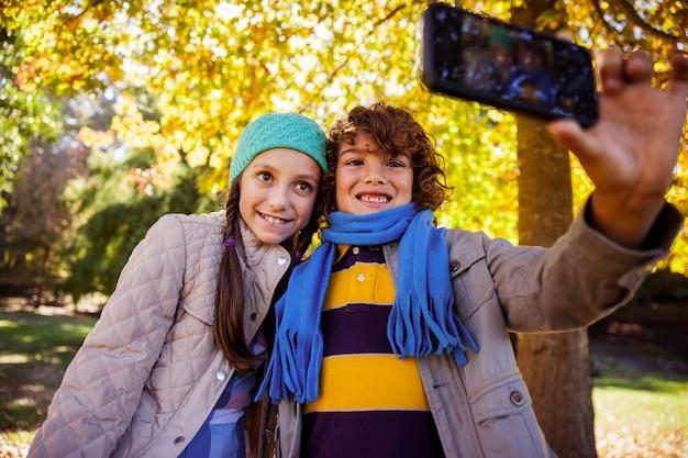 Hermanos felices tomando selfie en el parque durante el otoño