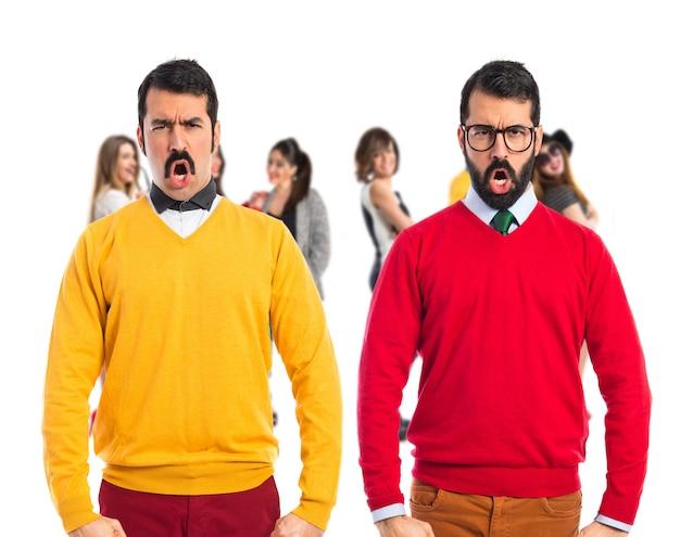 Hermanos gemelos con bigote gritando