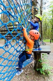 Hermanos gemelos escalada en el parque de aventura