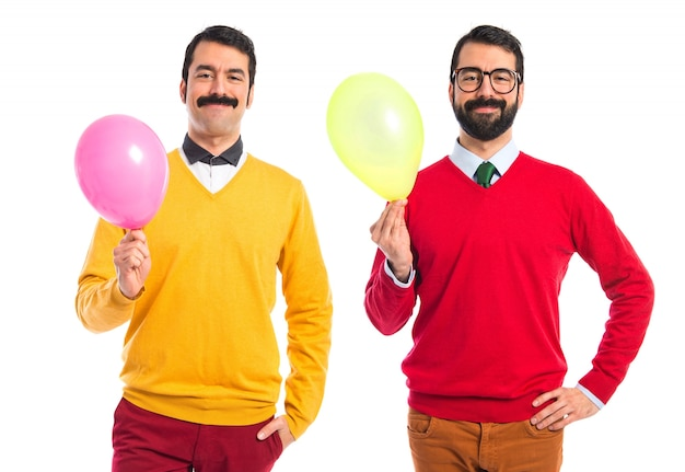 Hermanos gemelos con globos Foto gratis