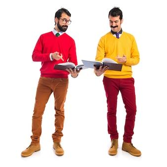 Hermanos gemelos leyendo libros