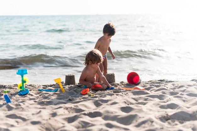 Hermanos haciendo castillos de arena junto al mar.