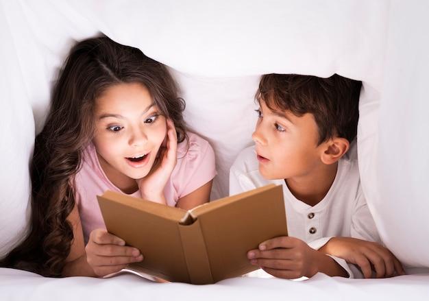 Hermanos a la hora de dormir leyendo cuentos