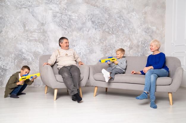 Los hermanos juegan con pistolas y corren alrededor de los abuelos en la sala de estar. nietos inquietos visitando parientes