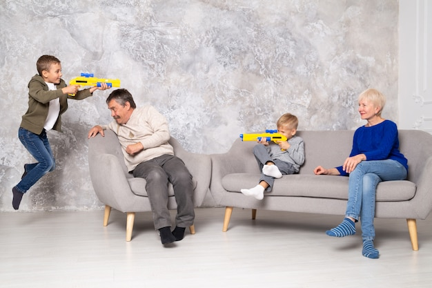 Los hermanos juegan con pistolas y corren alrededor de los abuelos en la sala de estar. un niño salta y dispara a su hermano por detrás del abuelo.