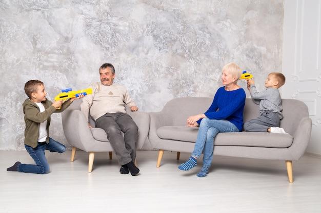 Los hermanos juegan con pistolas, corren alrededor de los abuelos en la sala de estar
