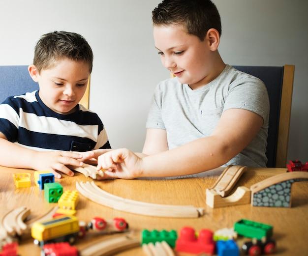 Hermanos jugando con bloques, trenes y coches.