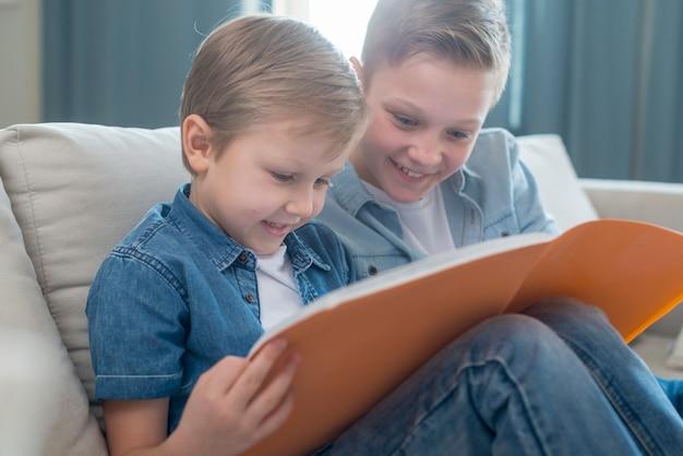 Hermanos leyendo un libro juntos