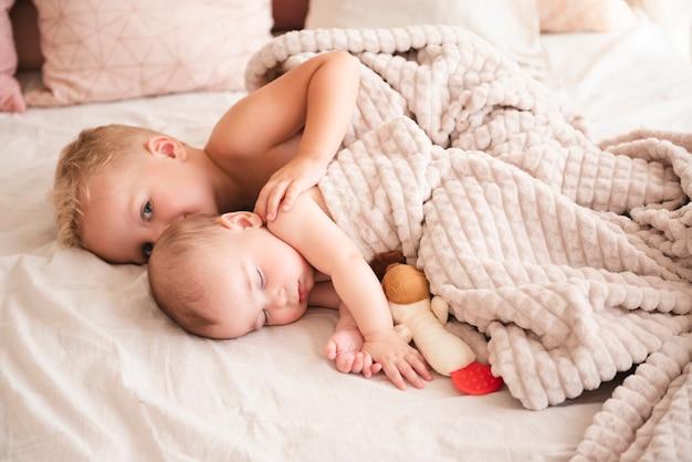 Hermanos lindos acostado en la cama
