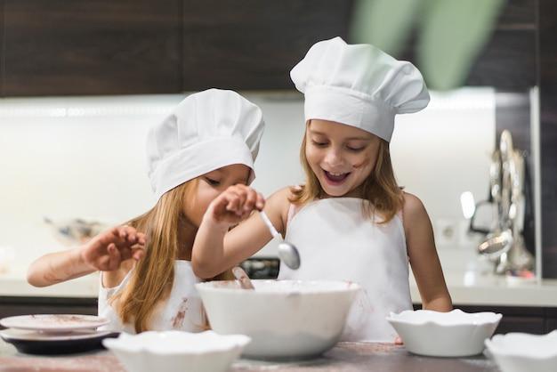Hermanos lindos felices que preparan la comida en encimera de la cocina