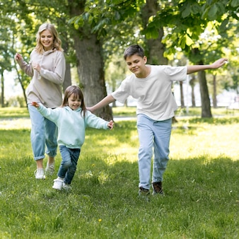 Hermanos y mamá corriendo juntos