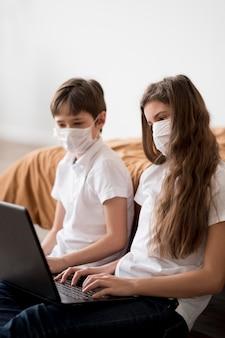 Hermanos con máscara usando laptop