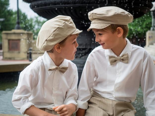 Hermanos con pajaritas y sombreros sentados en una fuente y mirarse en un parque