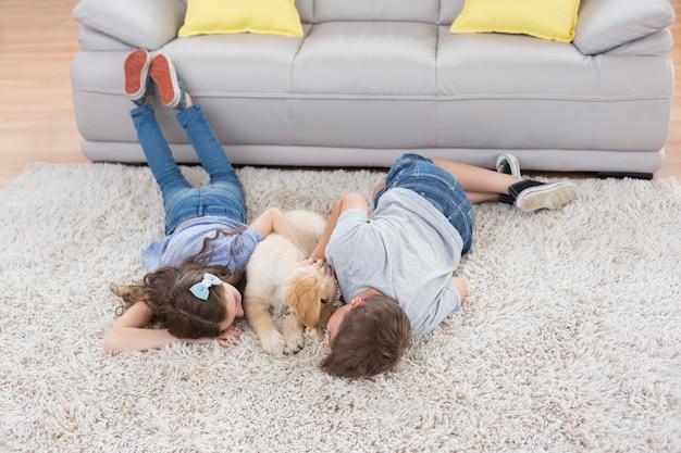 Hermanos con perro acostado en la alfombra