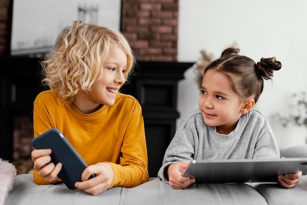 Hermanos en el sofá con tableta y móvil.
