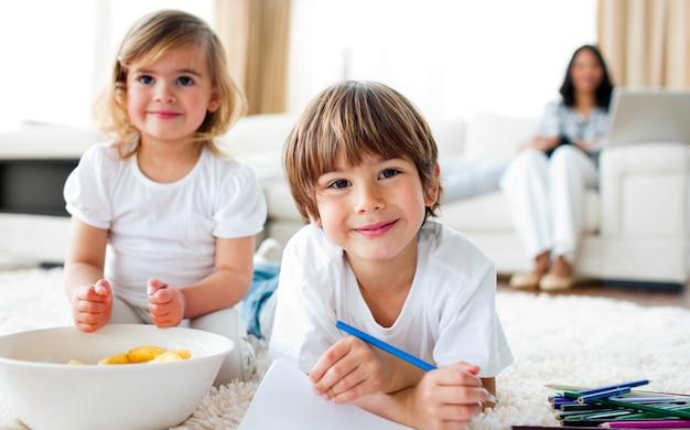 Hermanos sonrientes comiendo chips y dibujando