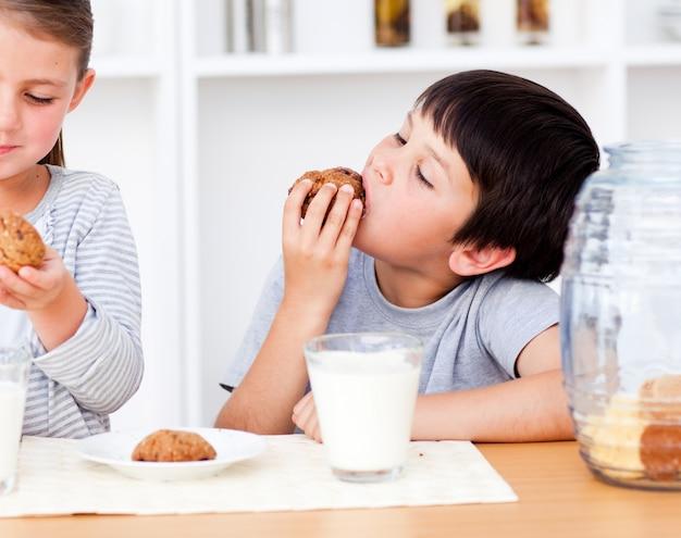 Hermanos sonrientes comiendo galletas y bebiendo leche