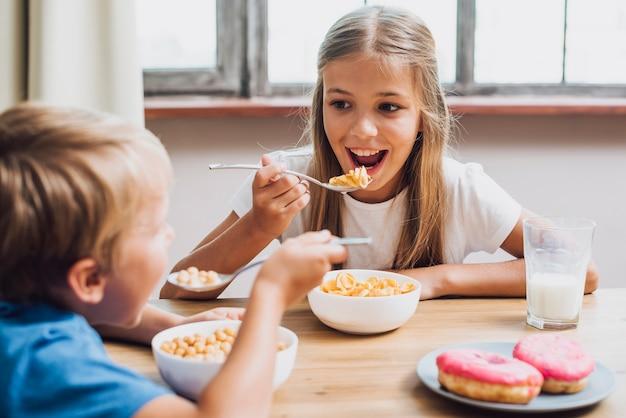 Hermanos sonrientes mirándose mientras comen