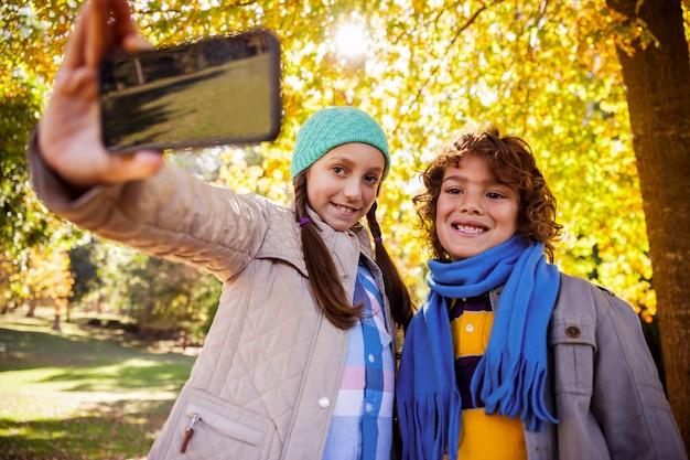 Hermanos sonrientes tomando selfie en el parque durante el otoño