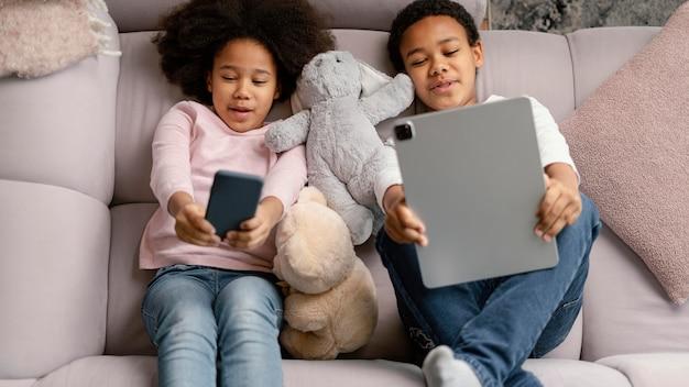 Hermanos con tableta y móvil en casa.